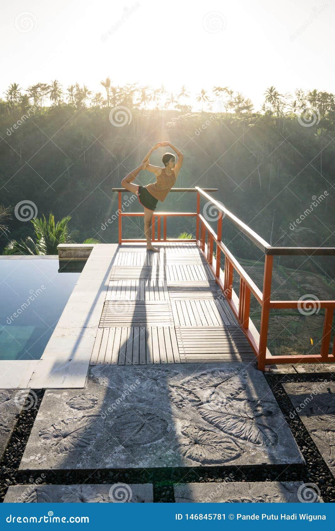 De mooie jonge Aziatische vrouw die yogaoefening met stellende Lord van Natarajasana van de dans doen stelt dichtbij zwembad met