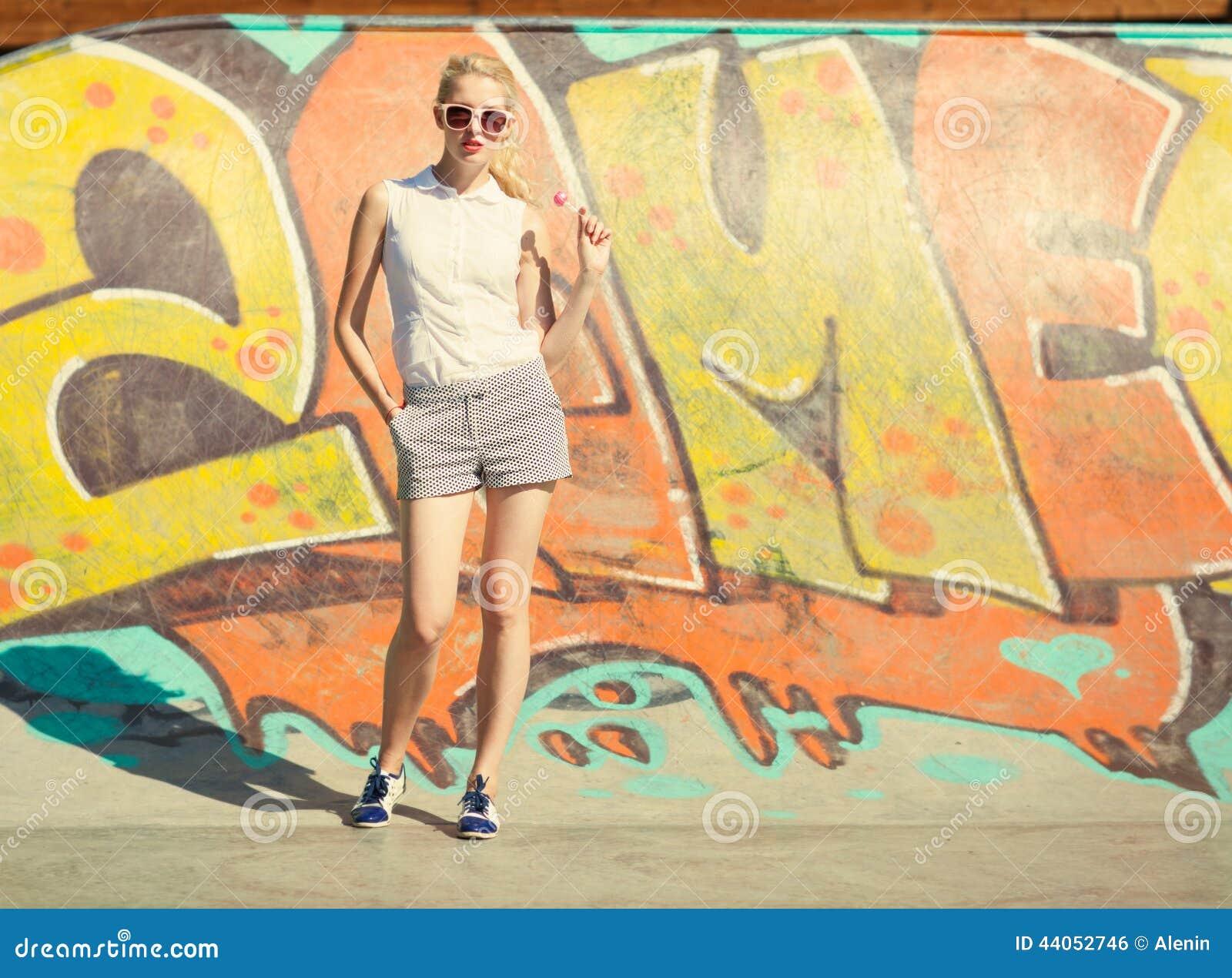 De mooie jonge blonde vrouw in zonnebril en een lolly bevindt zich op graffitiachtergrond Gestemd in warme kleuren