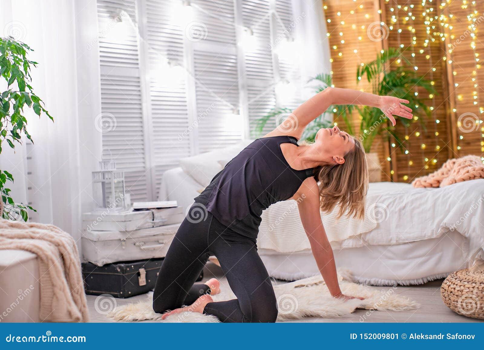 De mooie jonge blondevrouw, die de spieren van haar wapens en rug uitrekken, voert thuis gymnastiek- oefeningen uit met vrije tek