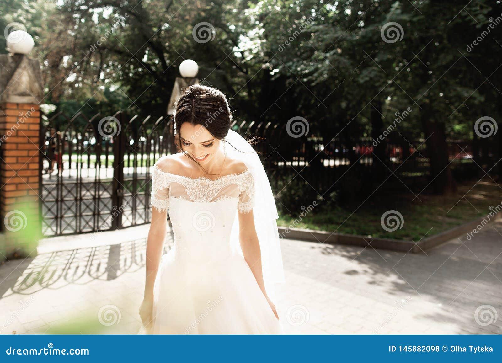 De mooie jonge bruid in modieuze witte kleding, het glimlachen ontmoet haar bruidegom in het park