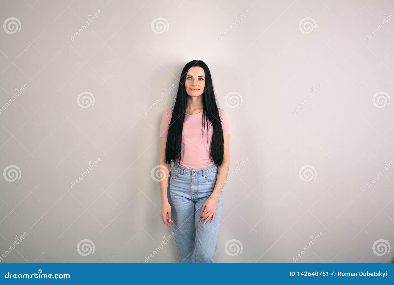 De mooie jonge donkerbruine vrouw met lang haar bevindt zich door de grijze achtergrond kijkend recht aan de camera wearing
