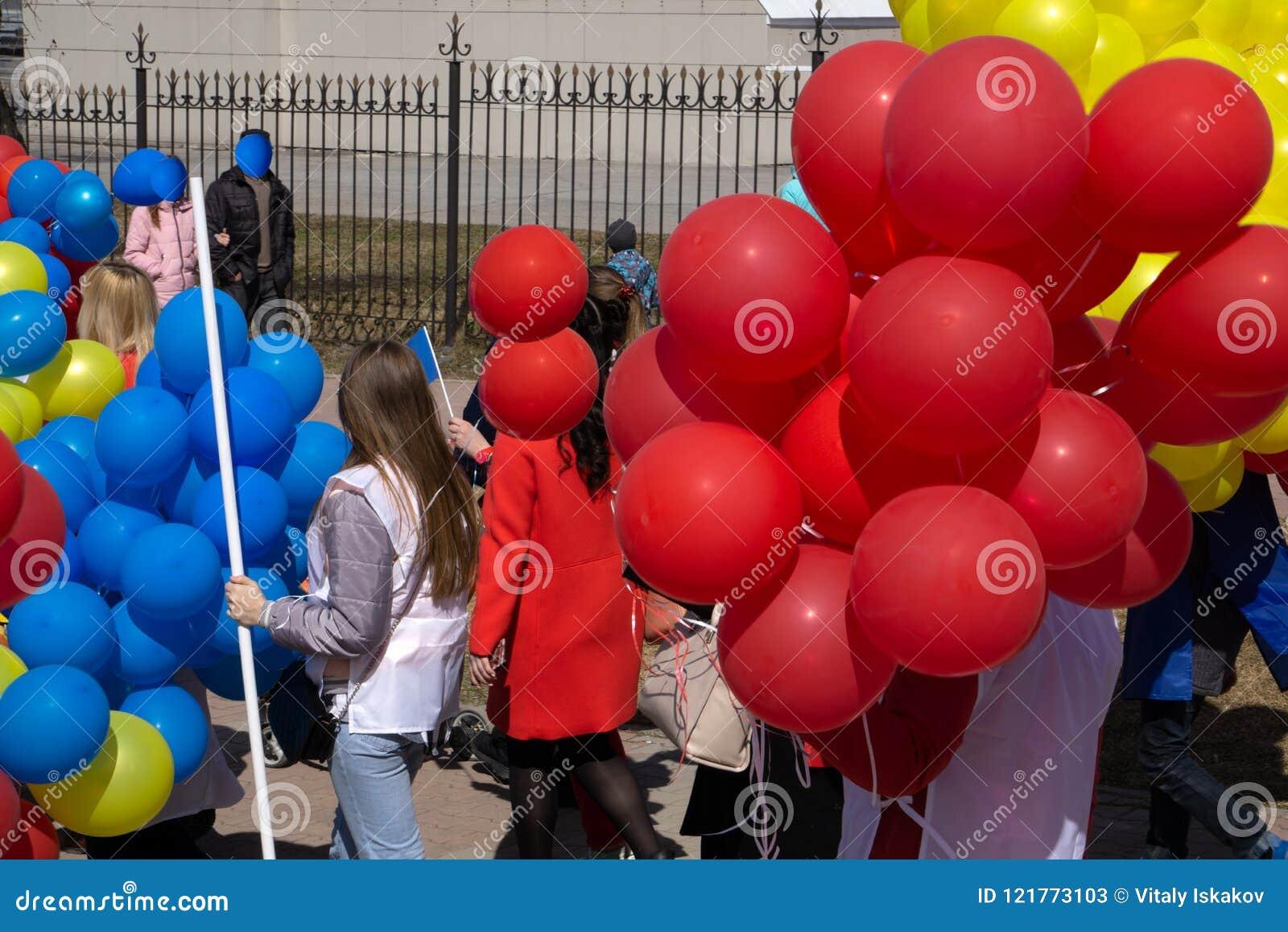 De mooie jonge meisjes gaan op een Carnaval-optocht bij een bloemfestival in een stadspark op een de zomerdag