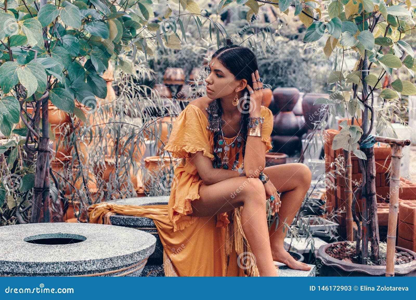 De mooie jonge modieuze vrouw met maakt omhooggaande en modieuze bohotoebehoren stellend op natuurlijke tropische achtergrond
