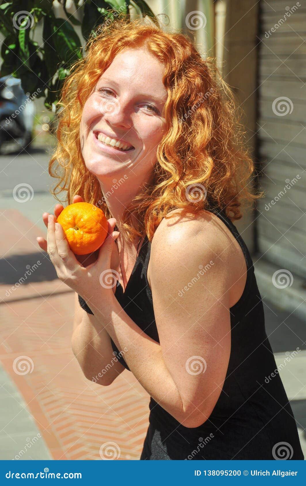 De mooie jonge roodharige vrouw, houdt gelukkig een zelf-geplukte sinaasappel indient binnen Ligurië Italië in de lente op vakant