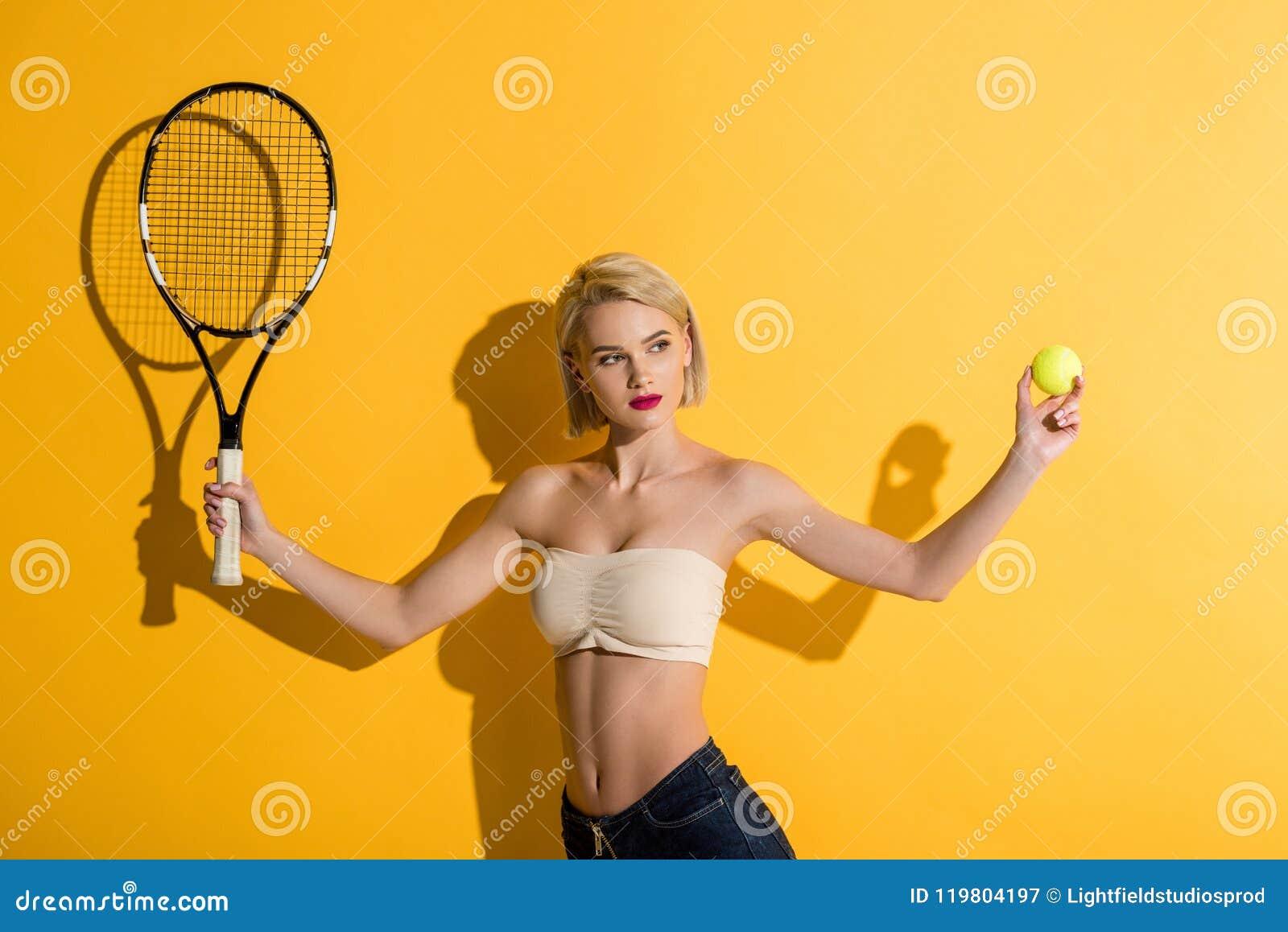 De mooie jonge van het de holdingstennis van de blondevrouw racket en de bal