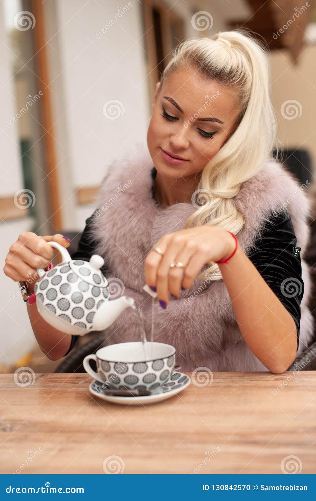 De mooie jonge vrouw drinkt thee op bar terace in de vroege herfst