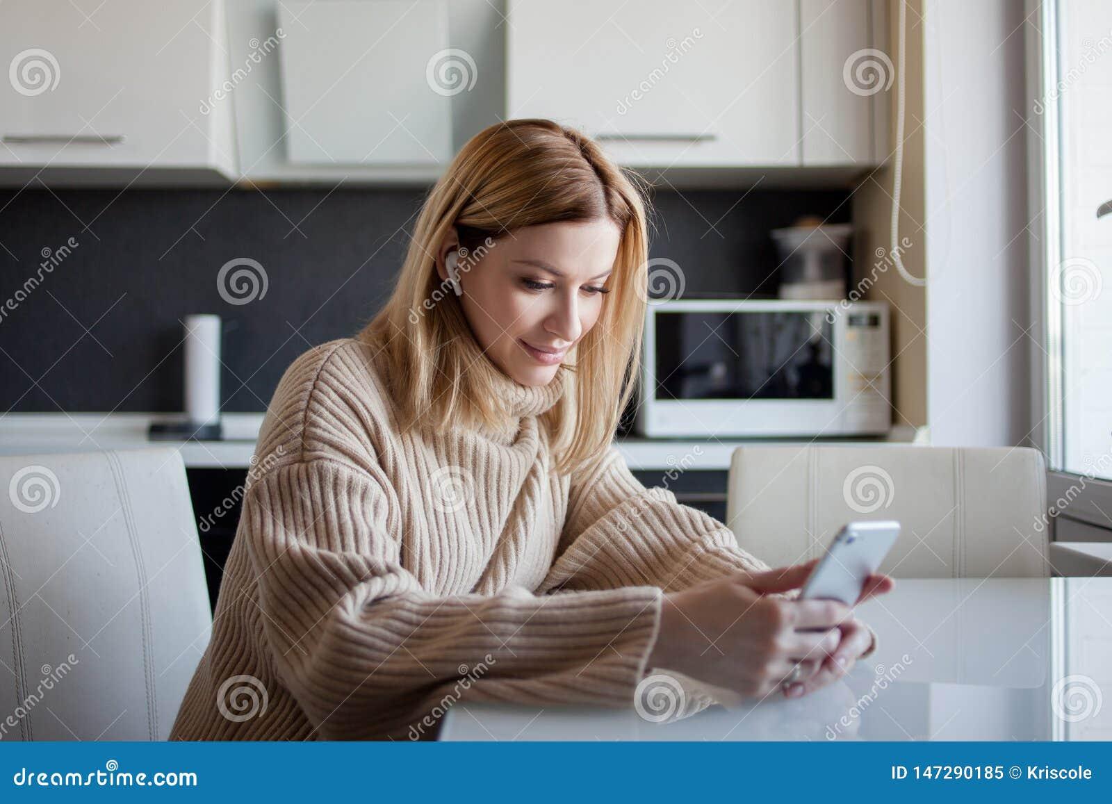 De mooie jonge vrouw in een comfortabele sweaterzitting in de keuken gebruikt de abonnementsdiensten en media toepassingen
