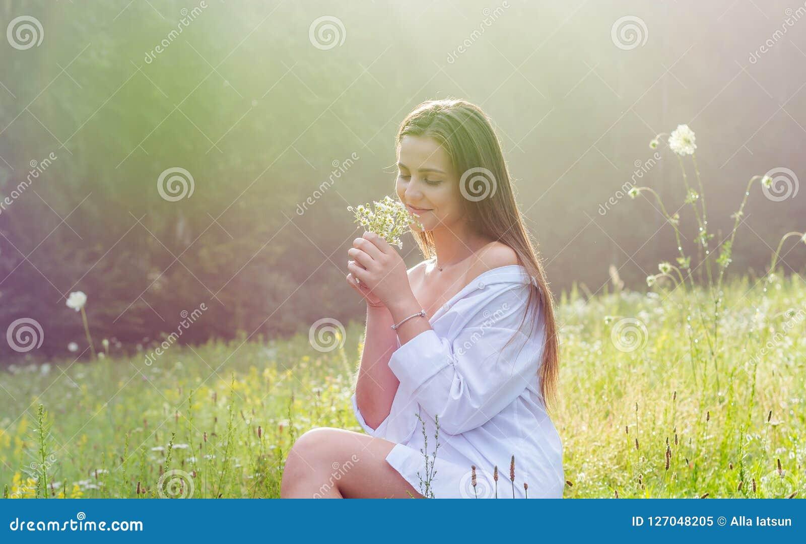 De mooie jonge vrouw in een wit overhemd houdt wilde bloemen i