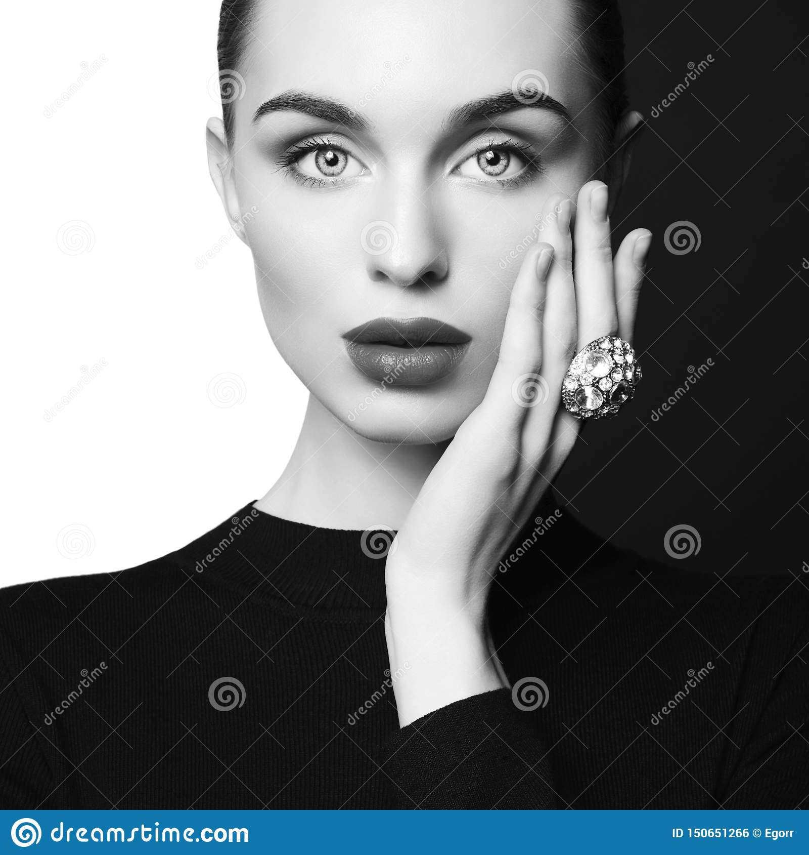 De mooie jonge vrouw met grote ring stelt in studio
