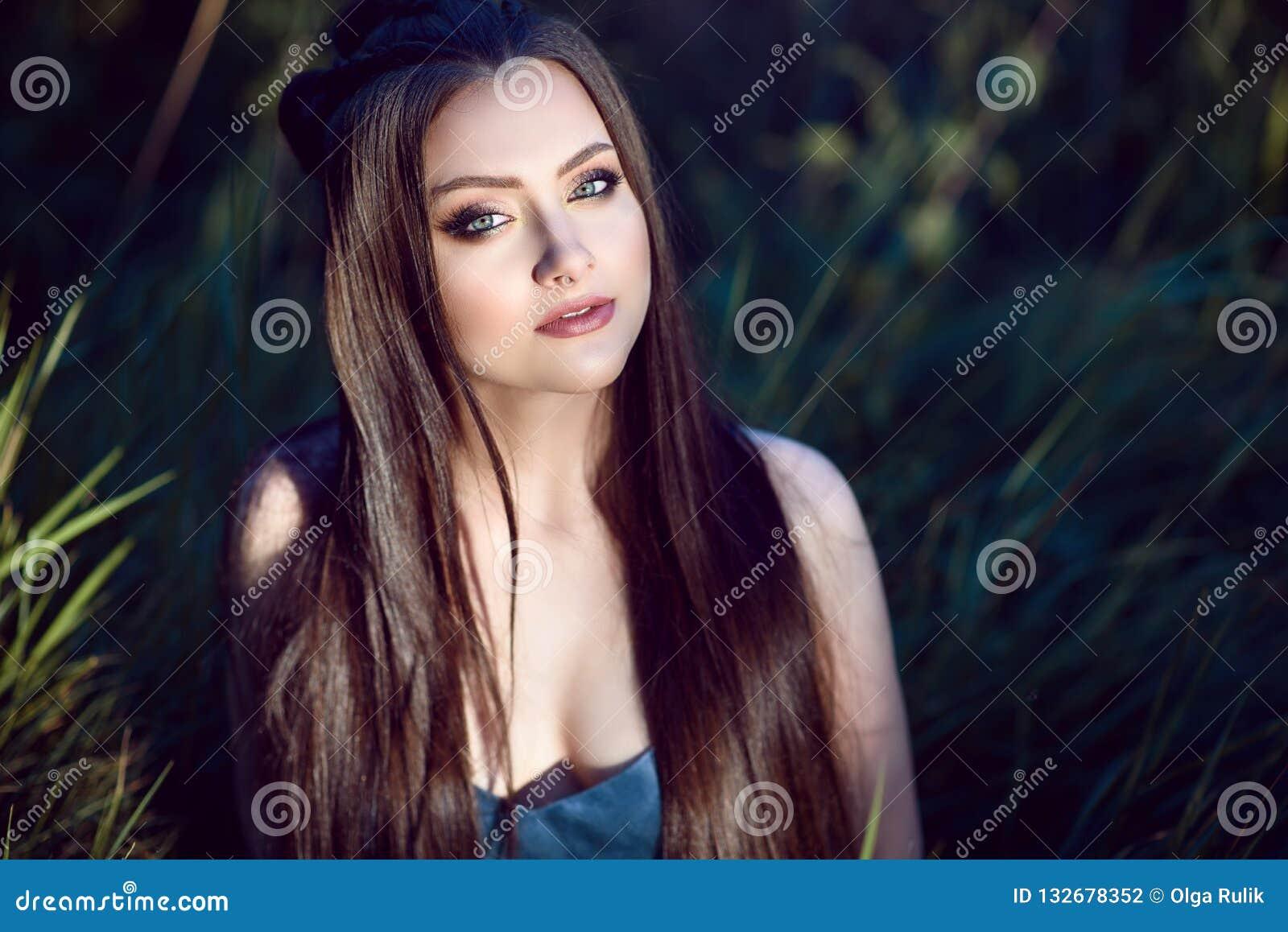 De mooie jonge vrouw met perfect maakt omhoog en snakt zijdeachtige rechte haarzitting op het gebied