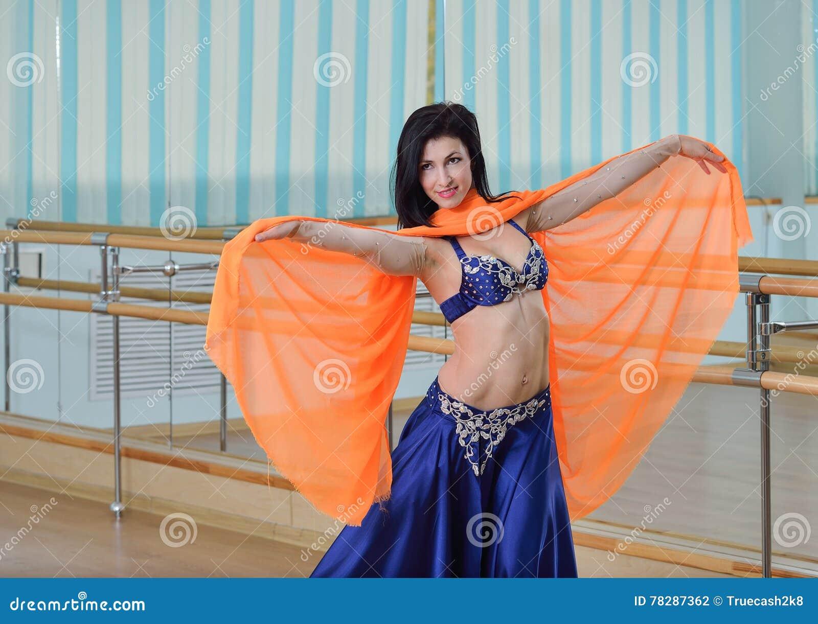 De mooie Kaukasische vrouw in kostuum voor buikdans danst binnen bij geschiktheidsklasse