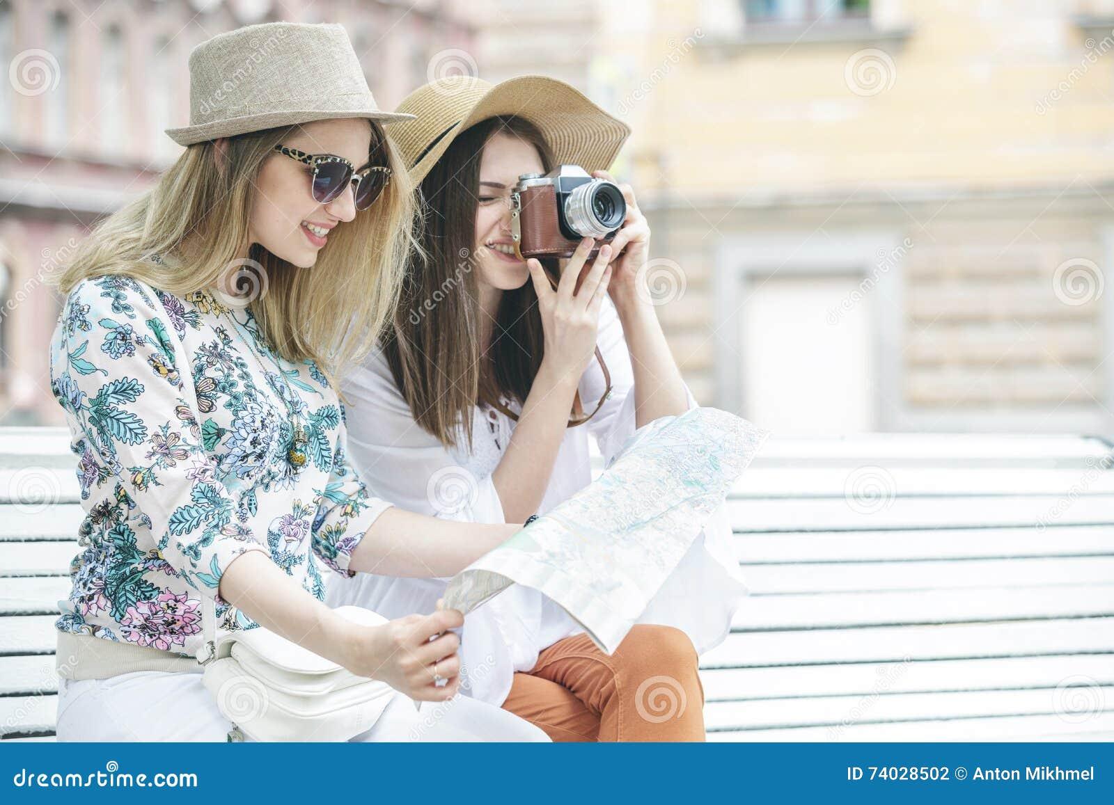 De mooie meisjestoeristen zoeken een adres op de kaartzitting op de bank