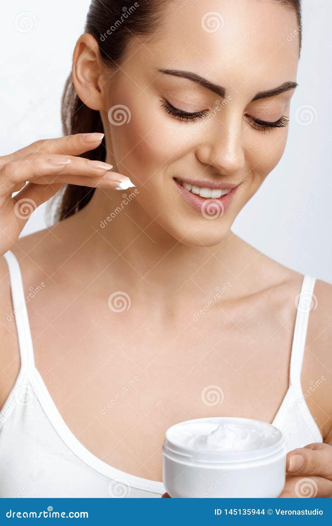 De mooie room van het vrouwengebruik voor huid Portret van aantrekkelijk wijfje met gezonde vlotte gezichts schone huid die een f