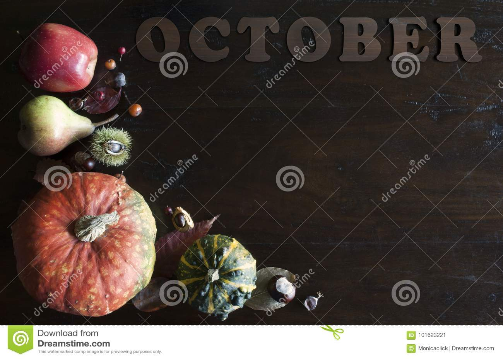De mooie rustieke dalingsvlakte legt met bladeren, pompoenen, kastanjes en brieven oktober op houten achtergrond