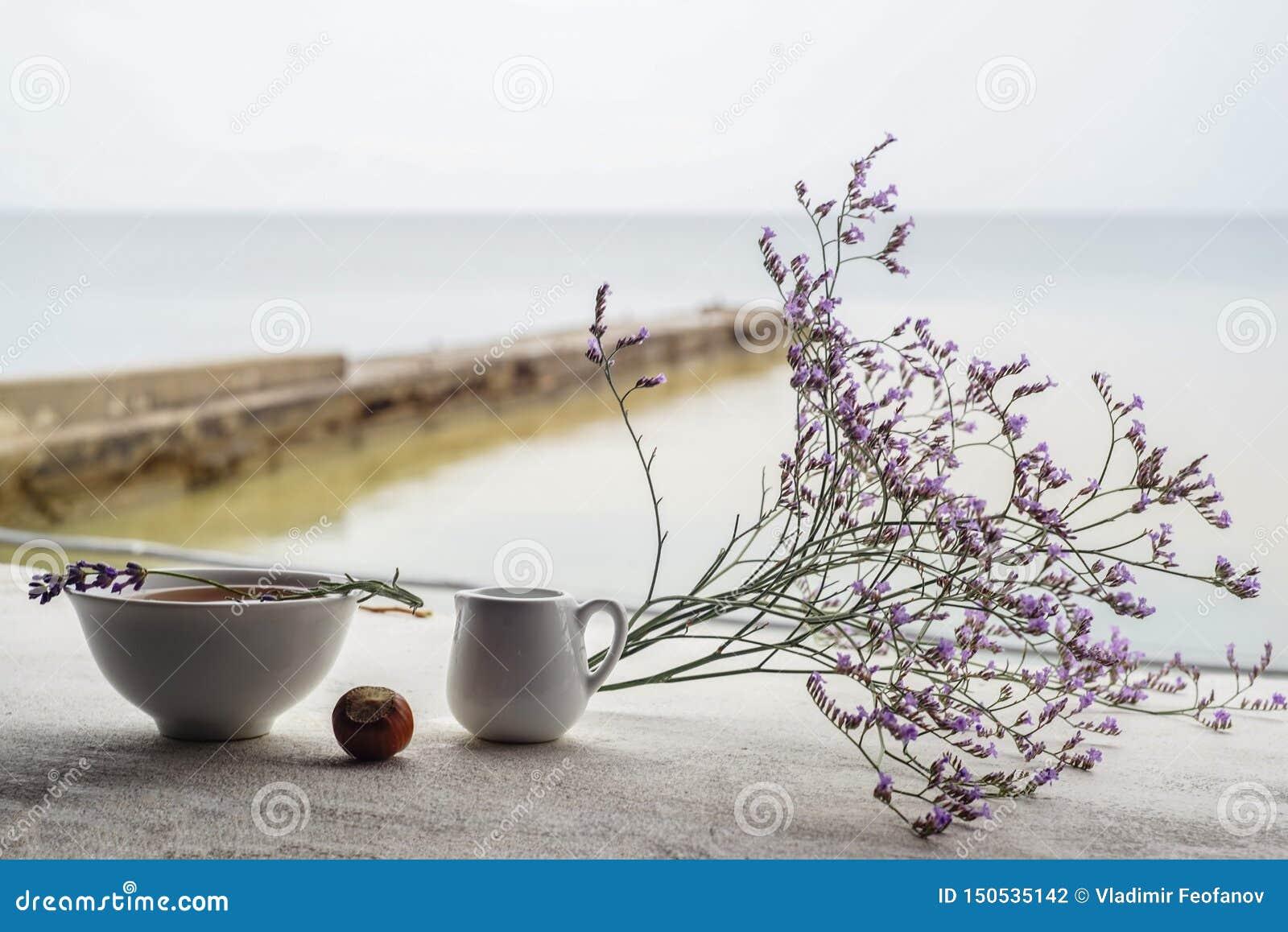 De mooie samenstelling van berglavendel bloeit en heerlijke lunch, hete soep in een witte plaat, een klein schip met zure room