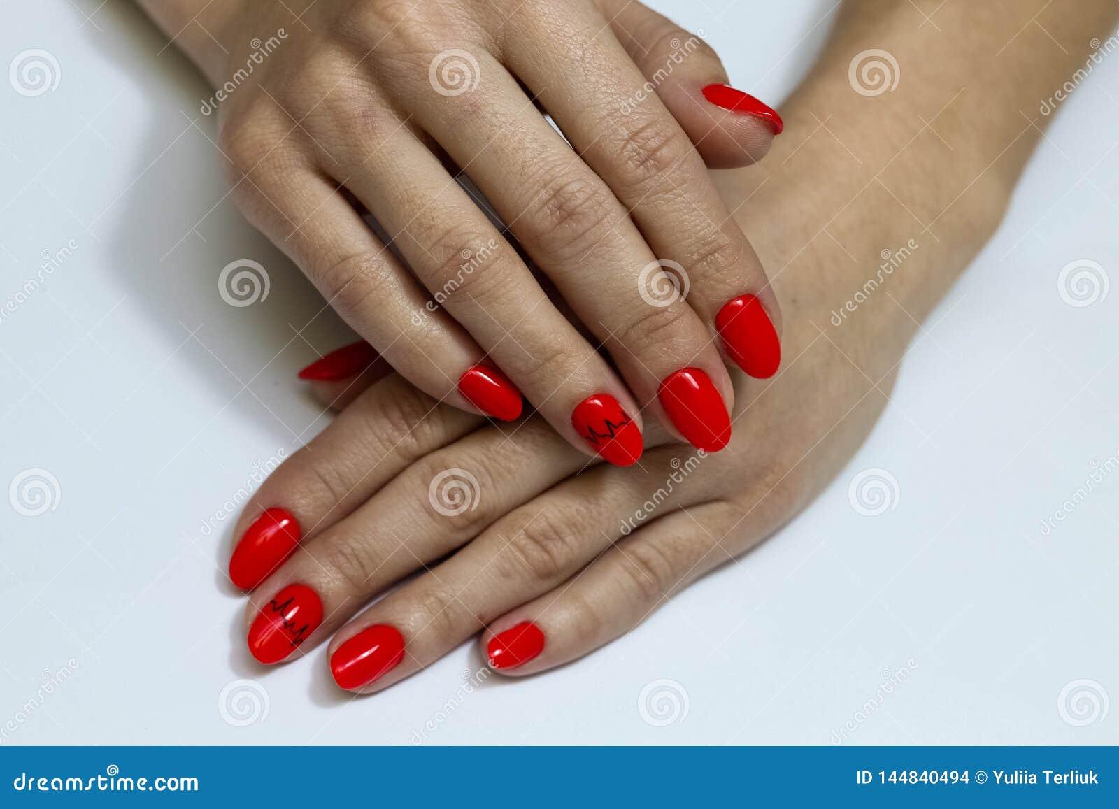 De mooie spijkers zijn behandeld met rode gellak Vrouw in een schoonheidssalon