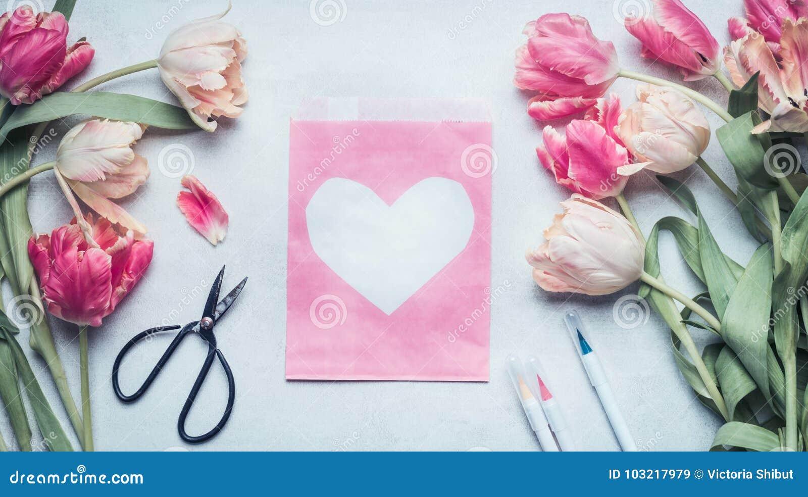 De mooie spot van de pastelkleurlente omhoog met tulpen, schaar, tellers en roze pakdocument zak met hart
