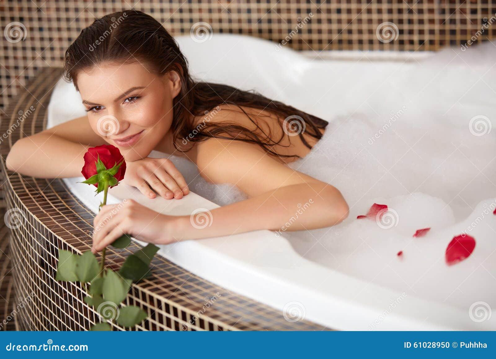 De mooie Vrouw in bad met nam toe De voet van de vrouw in het water