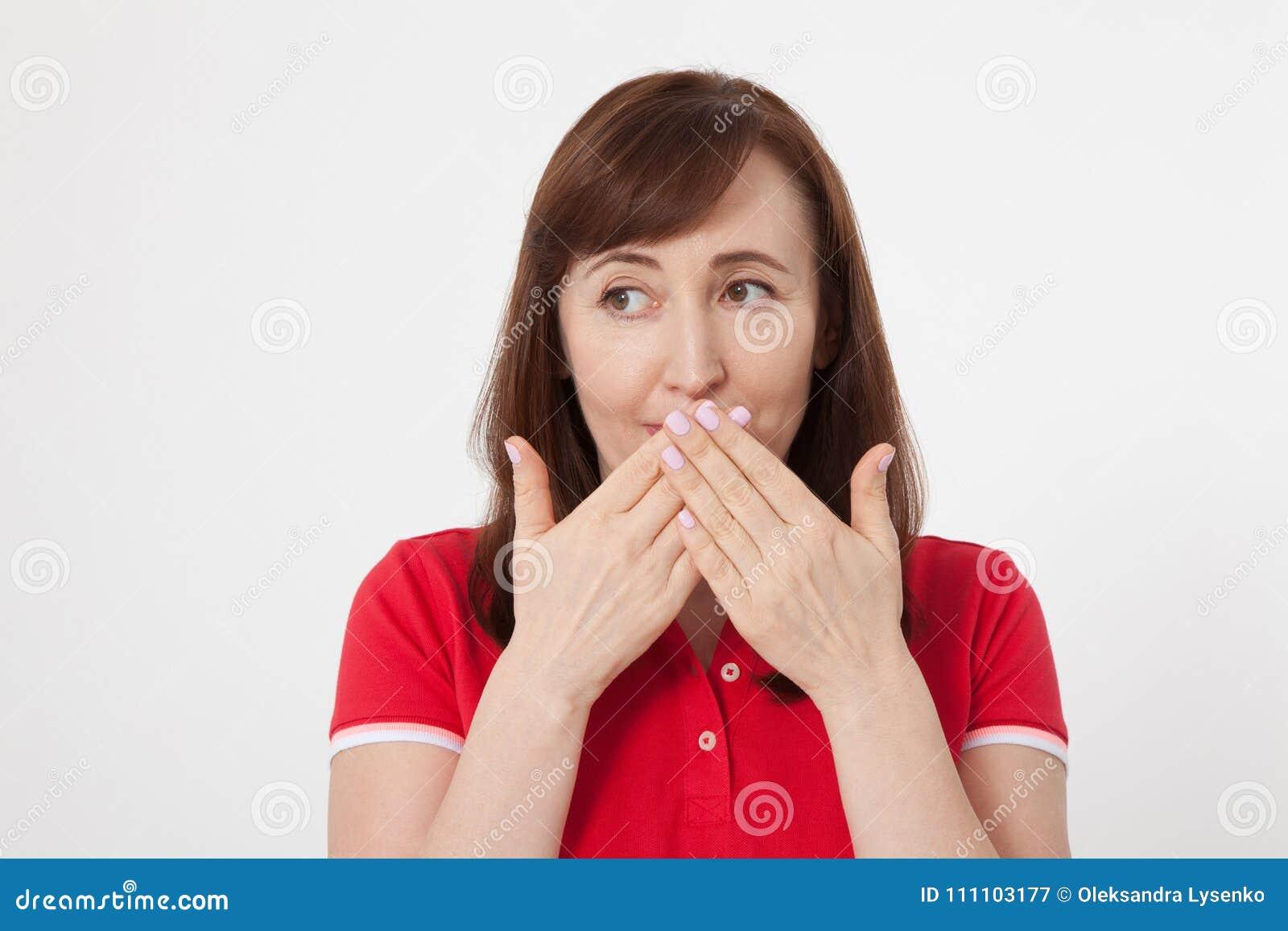 De mooie vrouw behandelt haar mond met haar handen voor geïsoleerd stil Rode t-shirt en het houden van een geheim