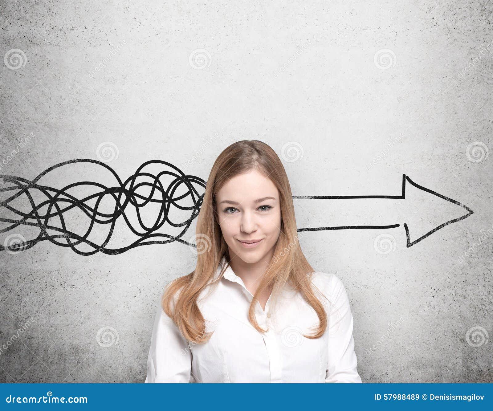 De mooie vrouw denkt over concept bedrijfsontwikkeling Een reusachtige pijl wordt getrokken op de concrete muur
