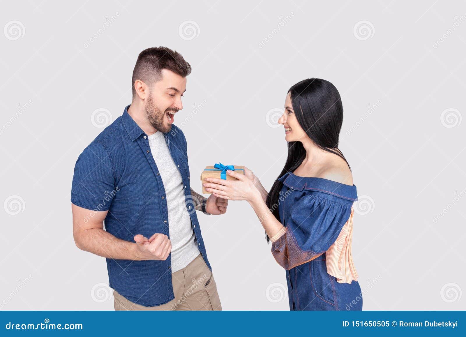 De mooie vrouw die haar vriend met gift verrassen isoleerde het dragen van denimkleding op askleurig-grijze achtergrond