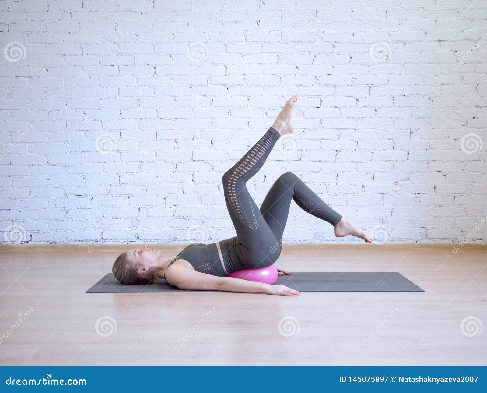 De mooie vrouw die van Yong pilates training met kleine roze geschiktheidsbal doet, de oefening van de beenboog Binnen, zolderach