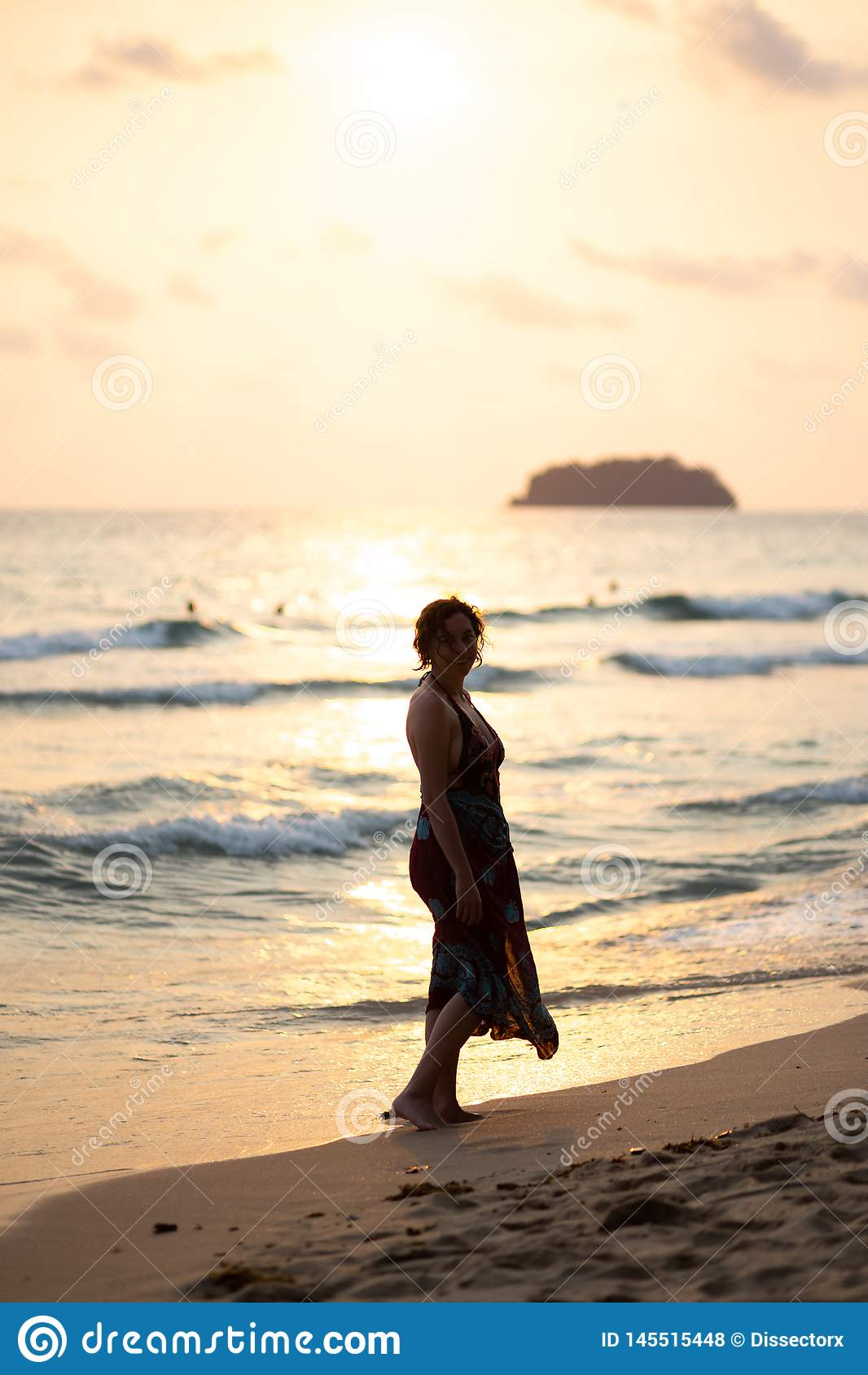 De mooie vrouw in een kleurrijke de zomerkleding die op het strand van Thailand Ko Chang met mooi wit lopen verzendt tijdens a