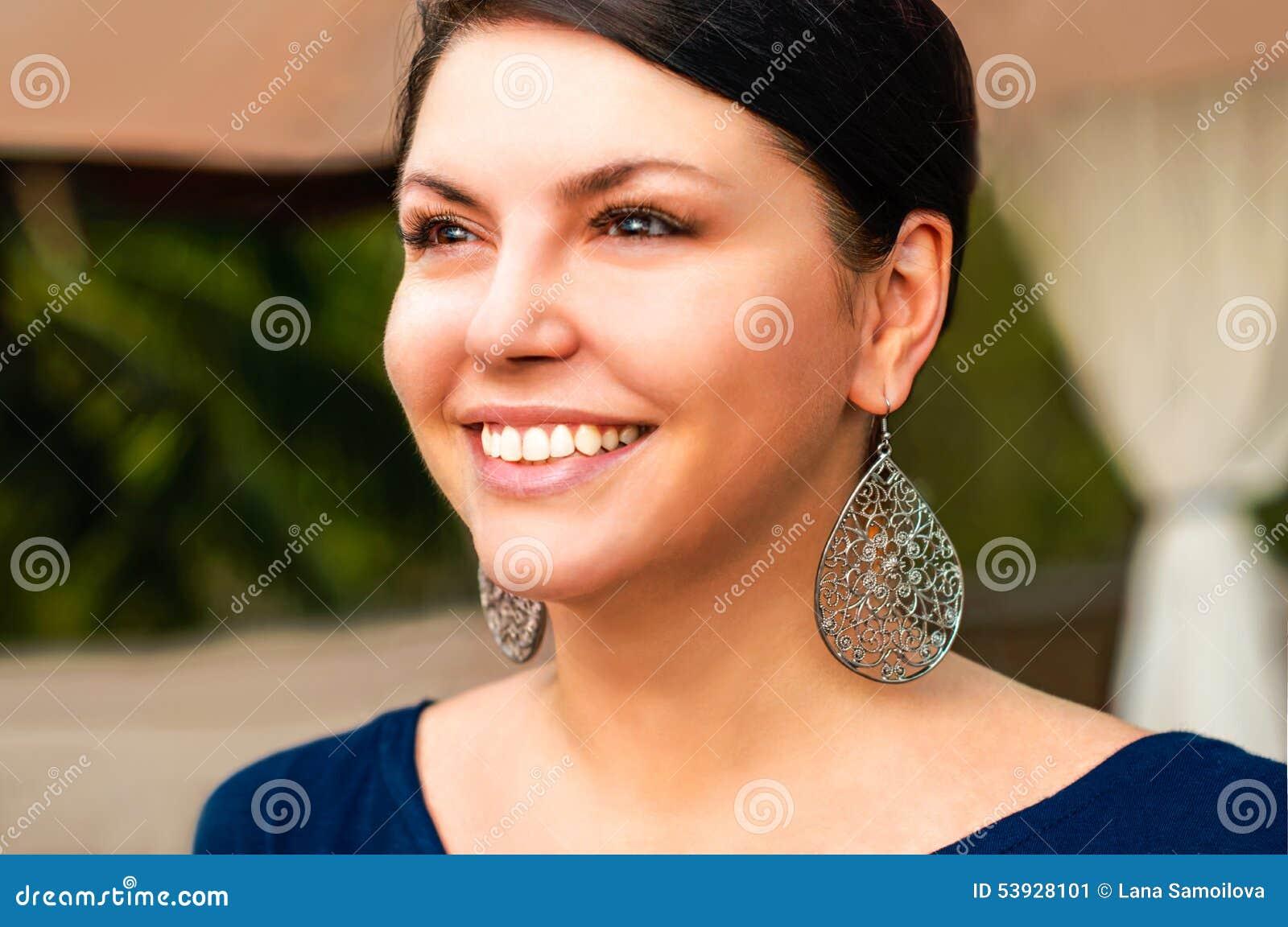 De mooie vrouw kijkt zijdelings en lacht