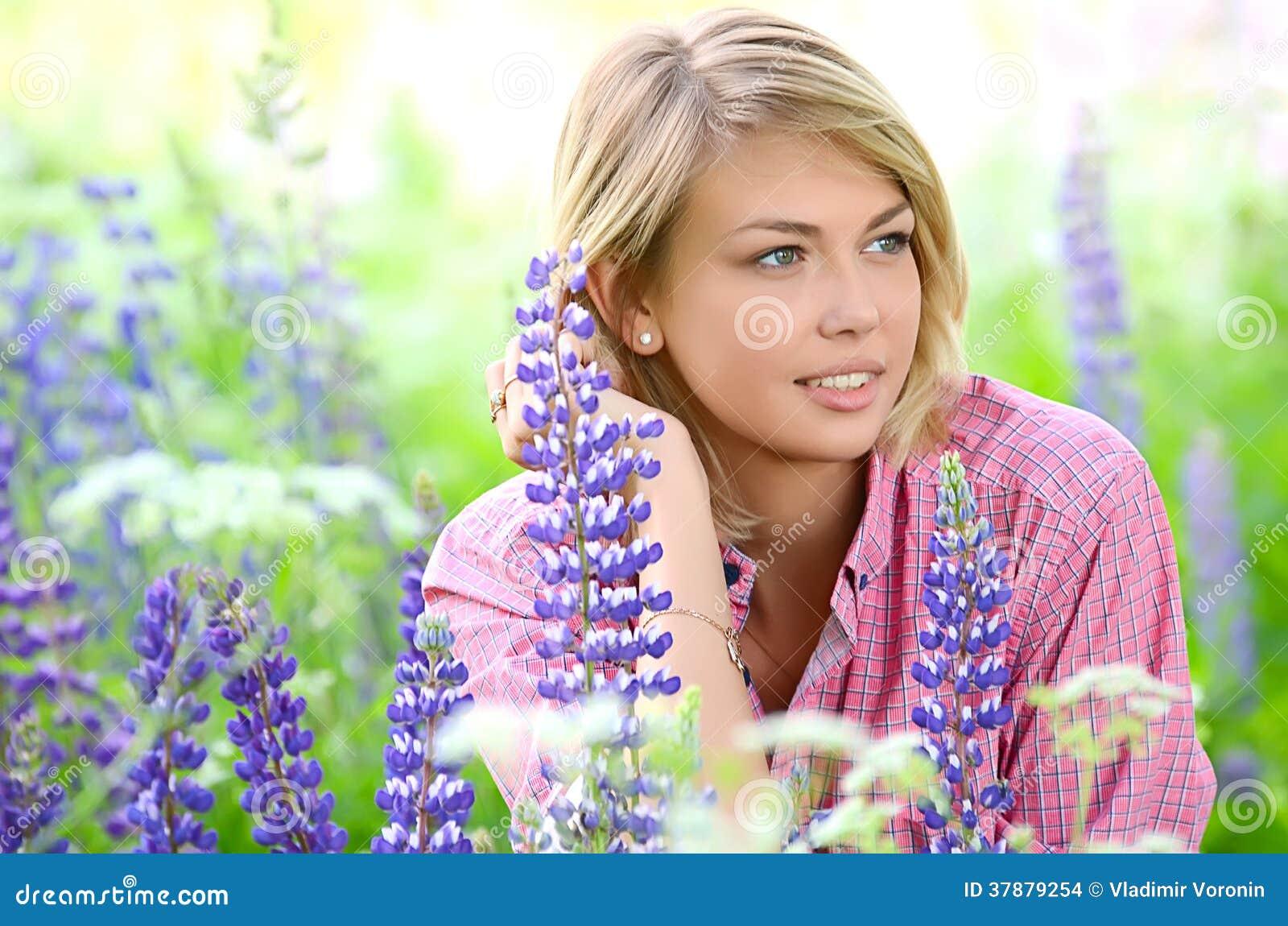 De mooie vrouw op het gebied met lupine