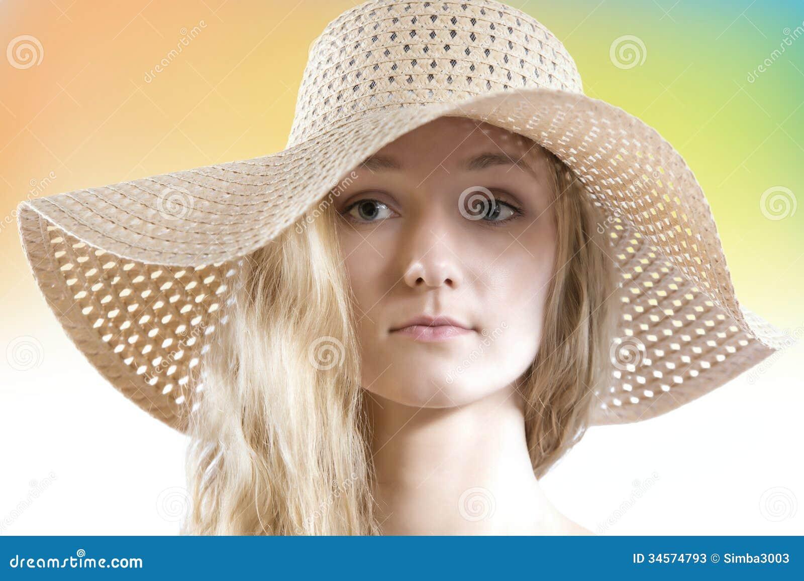De mooie vrouw zonder maakt omhoog het dragen van de hoed van de strozomer