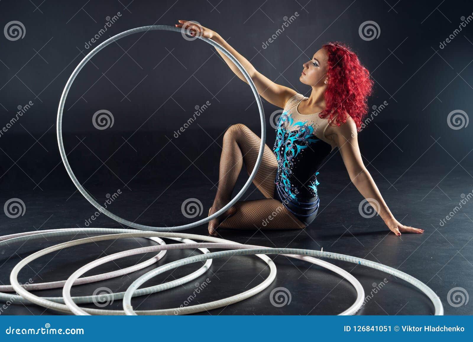 De mooie vrouwelijke rode kunstenaar van het haarcircus met hoepels