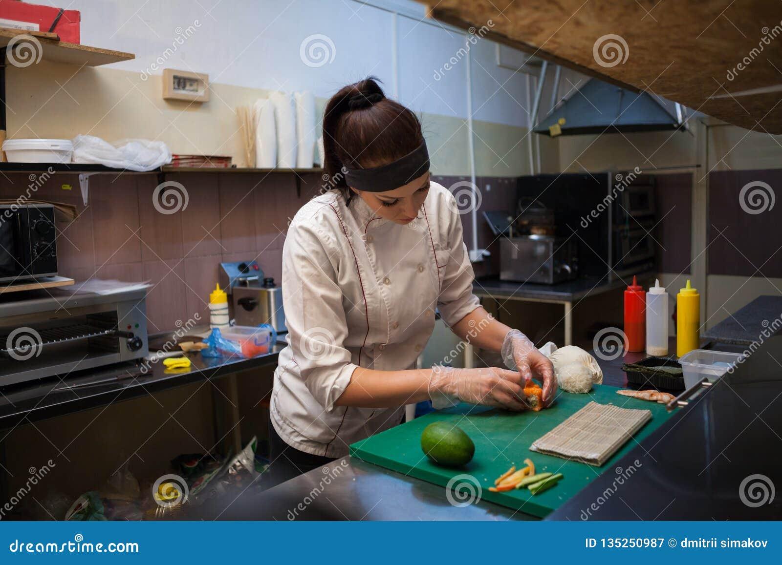 De mooie vrouwenchef-kok bereidt verse sushi in de keuken van het restaurant voor