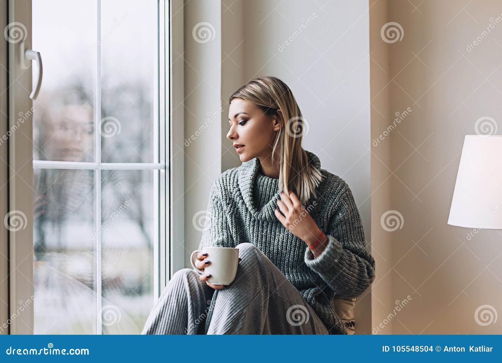 De mooie witte modieuze vrouw in comfortabele Skandinavische interrior zit thuis dichtbij het grote venster, portret van mooi