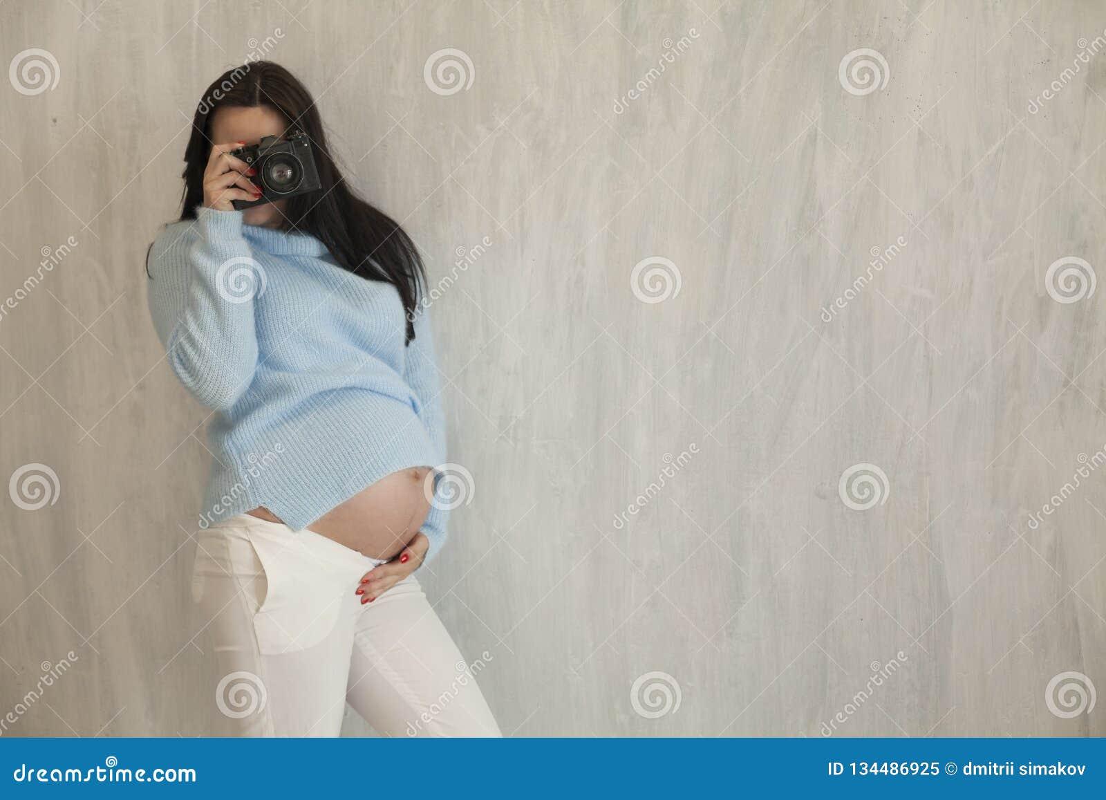 De mooie zwangere vrouw neemt een beeld op de camera