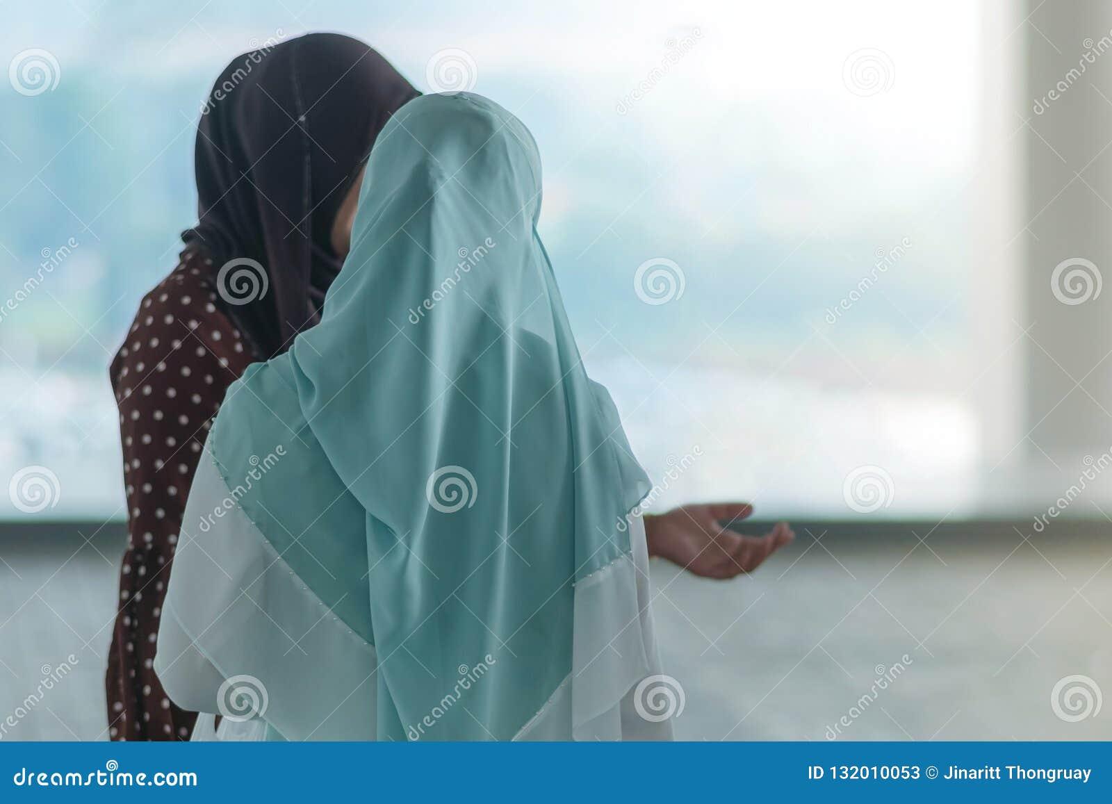 De moslimvrouwen wachten op vrienden samen te reizen