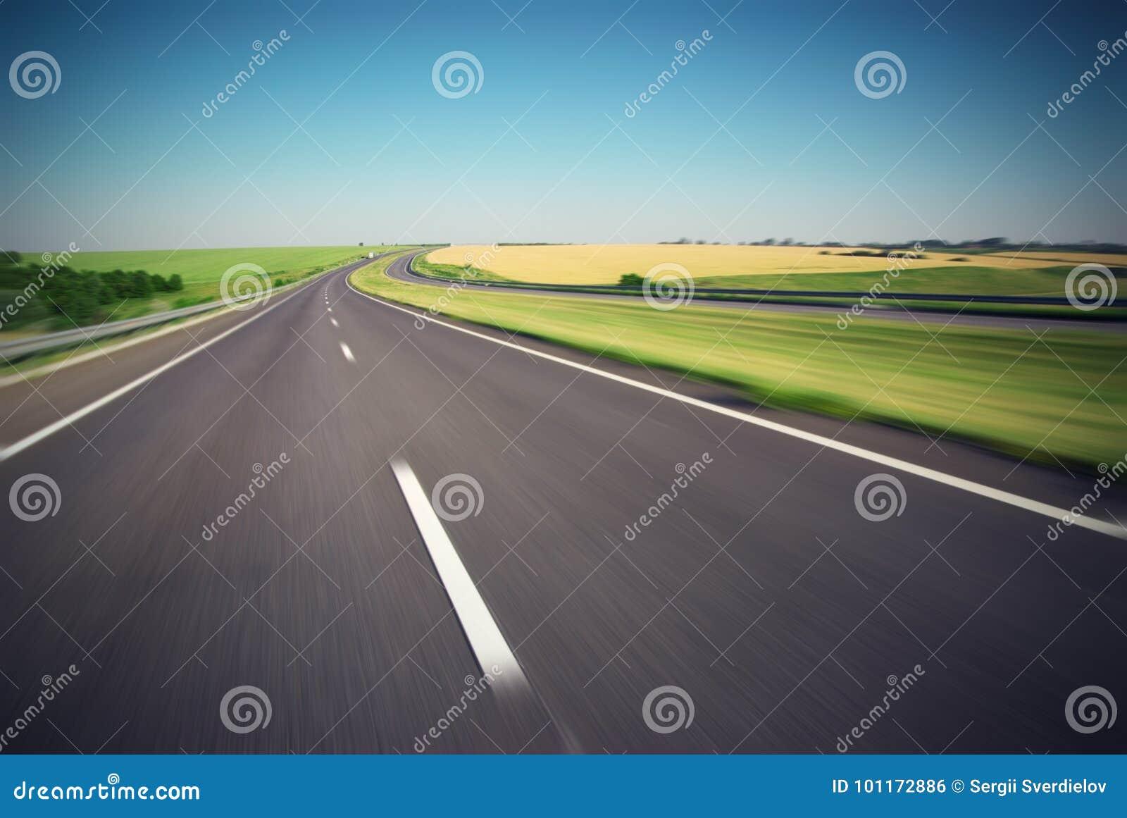 De motie vertroebelde lege weg met groene weide op horizon