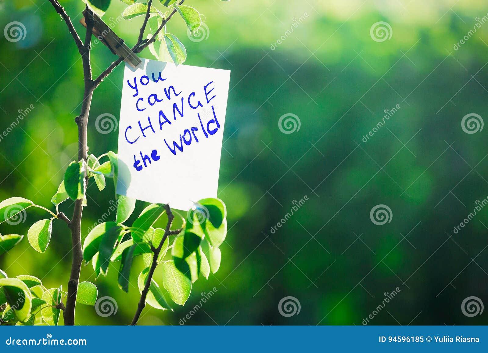 De motiverende uitdrukking u kan de wereld veranderen Op een groene achtergrond op een tak is een Witboek met een motiverende uit