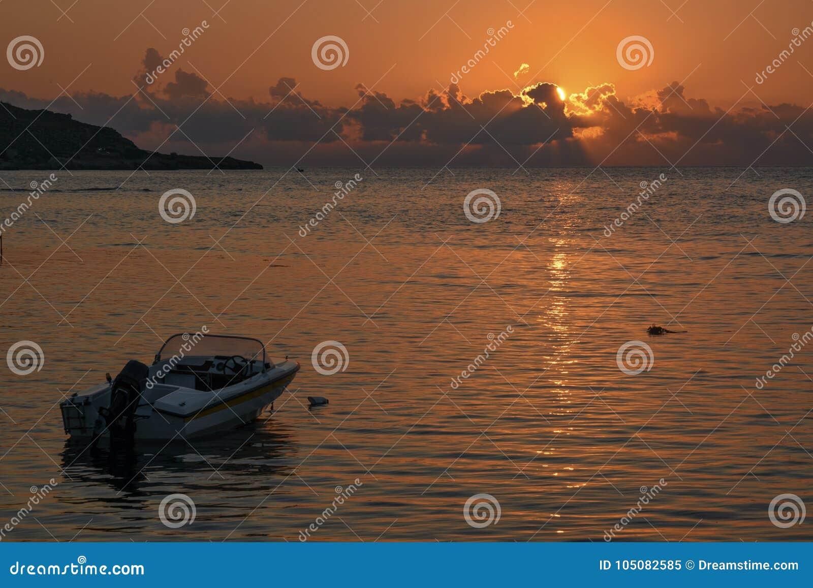 De motorboot bij zonsondergang