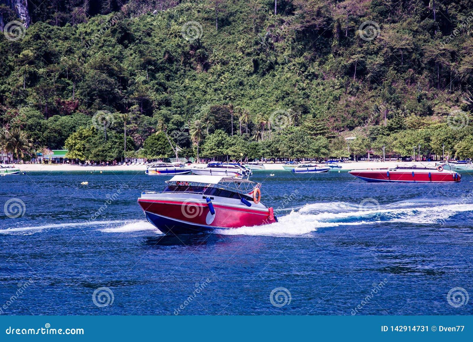 De motorboot versnelt Vlotters vanaf de kust, die achter hem grote golven verlaten