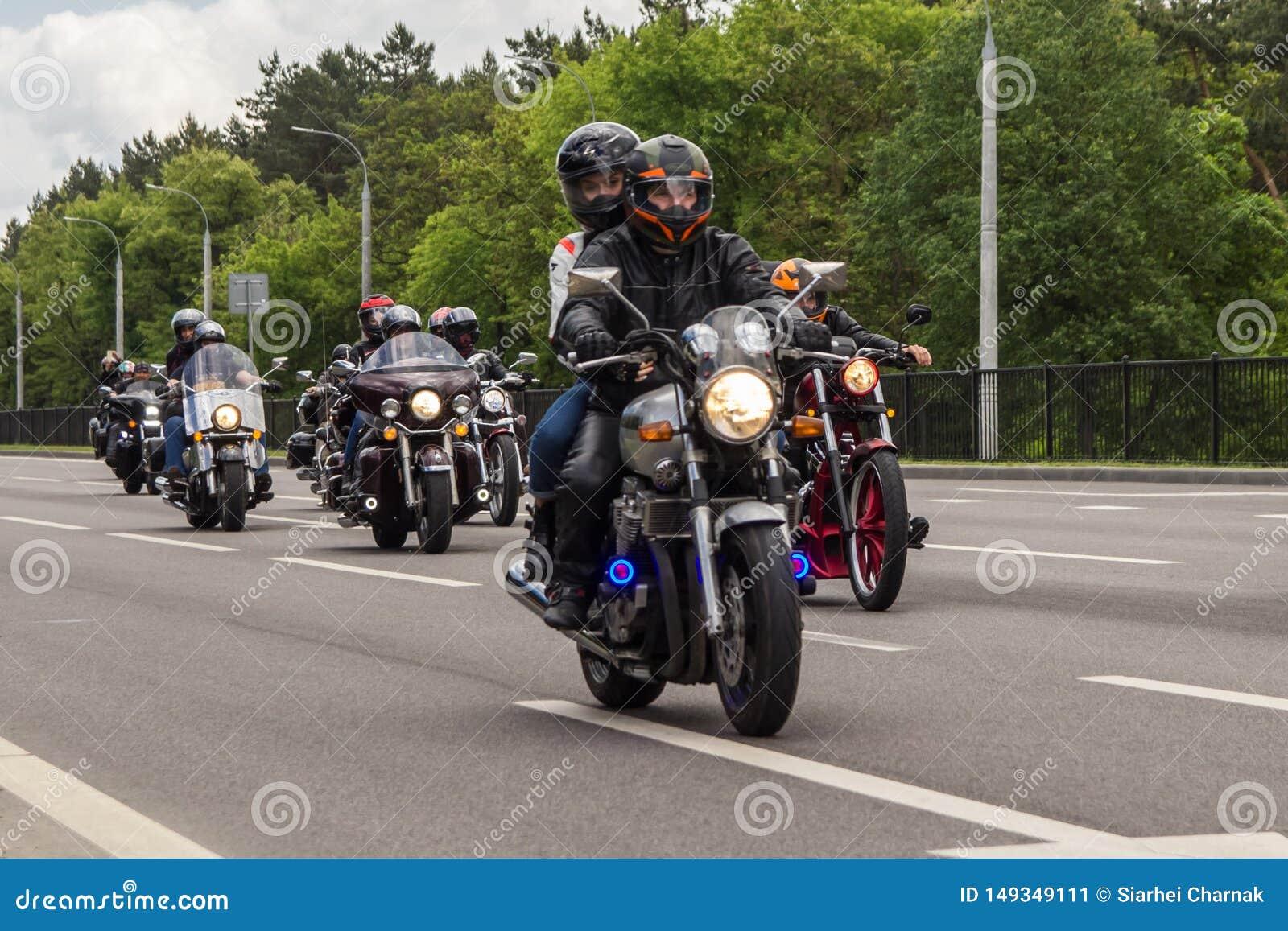 De motorfietsfietsers berijden op de weg op de rand van de stad