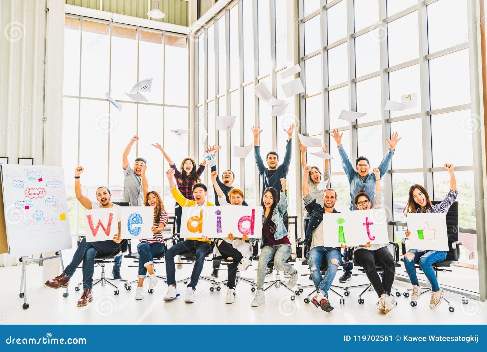 De multi-etnische diverse groep gelukkige bedrijfsmensen die, viert projectsucces met documenten schreef woorden samen toejuichen