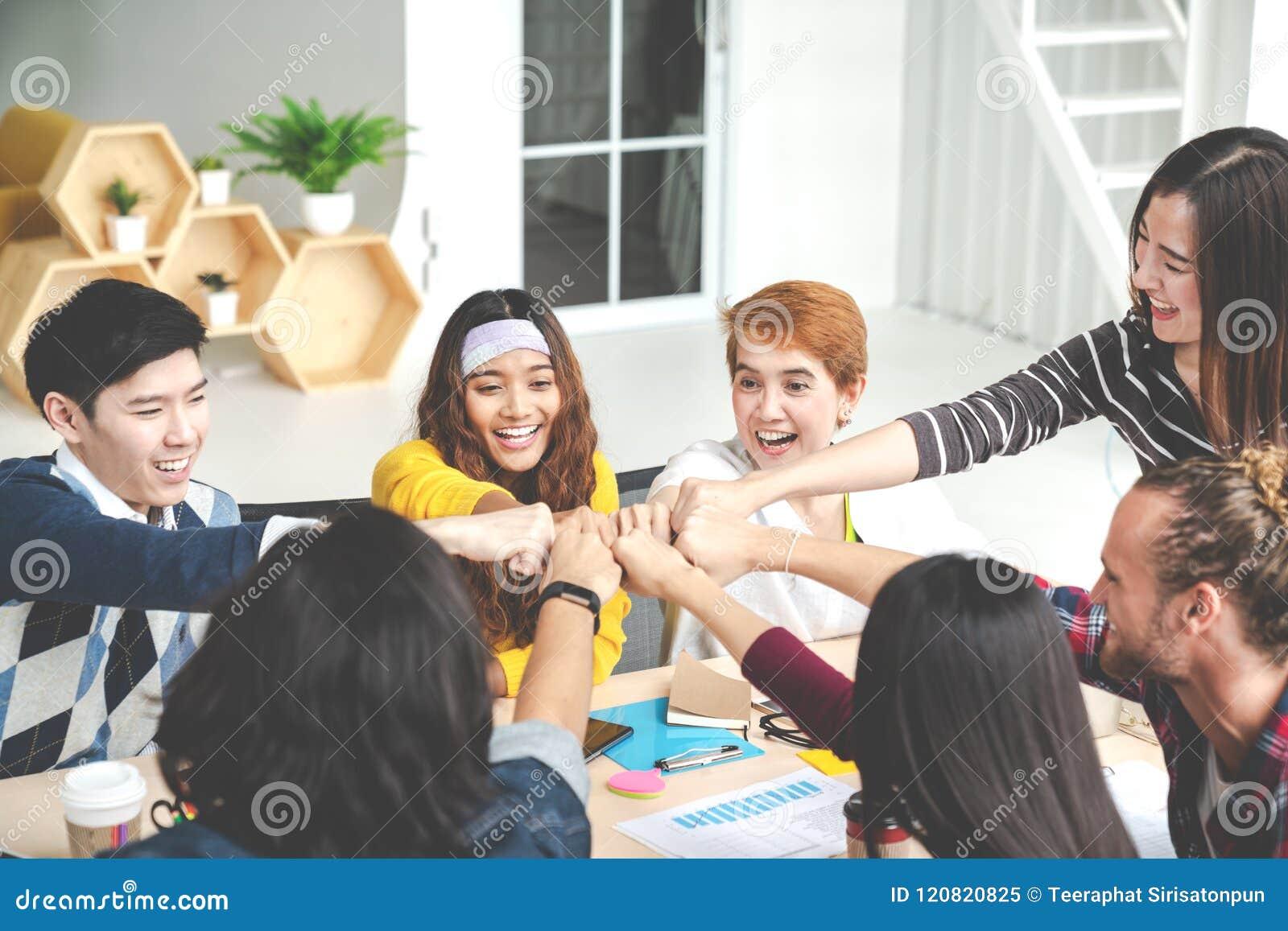 De multi-etnische jonge handen van de teamstapel samen als eenheid en groepswerk in modern bureau De diverse samenwerking van de