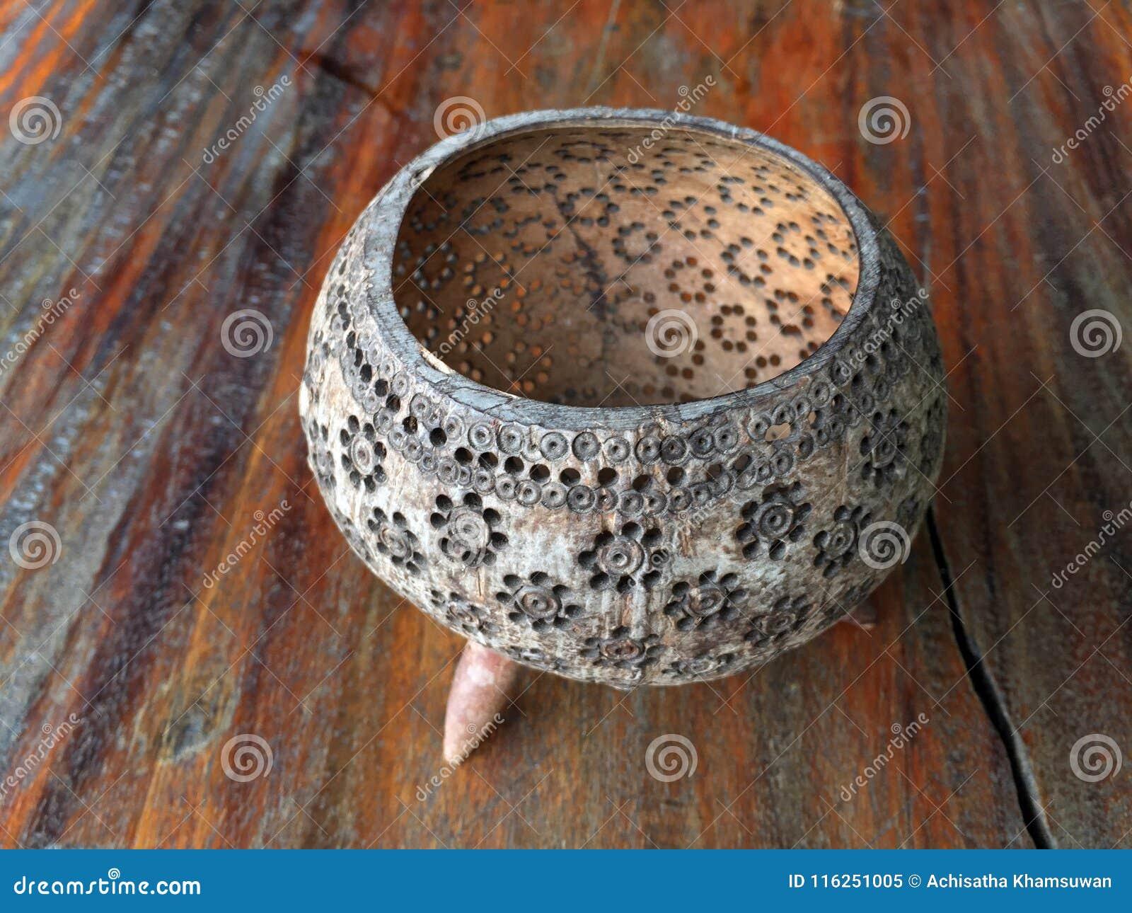 De multifunctionele houder maakte van shell van de kerfkokosnoot, het ontwerp van het bloempatroon, op de houten lijst