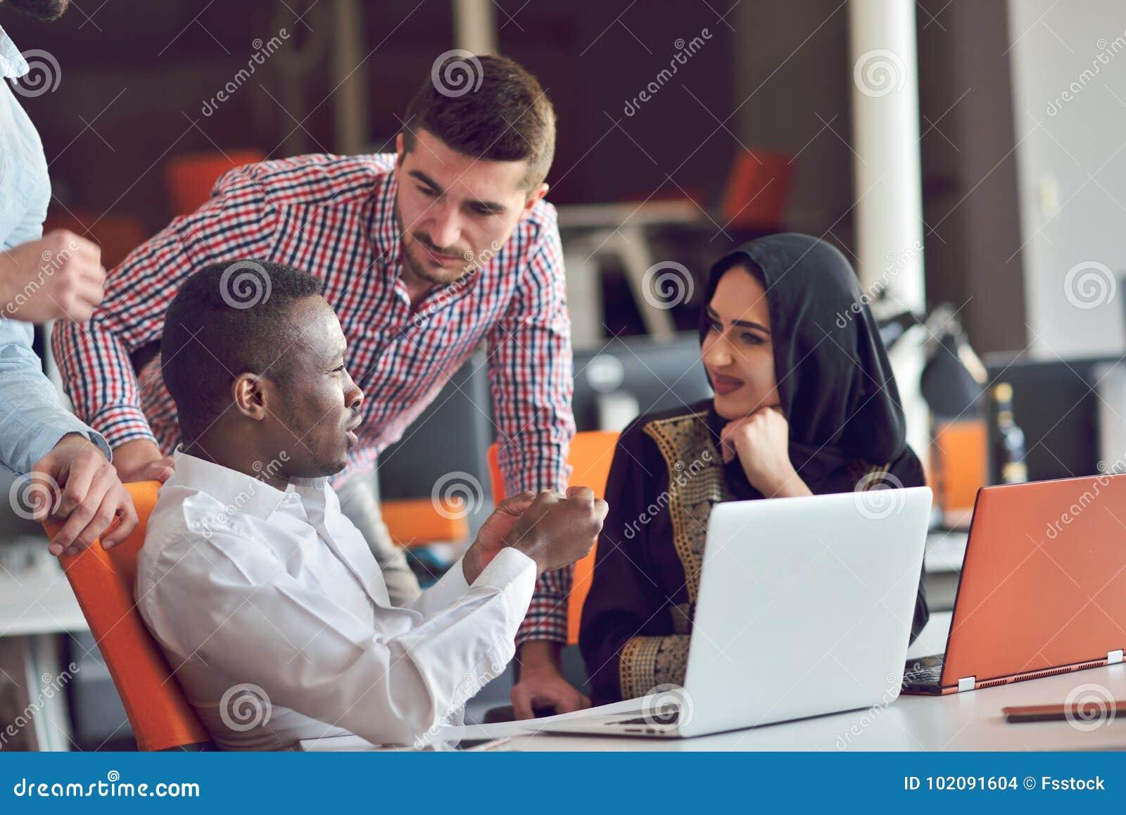 De multiraciale eigentijdse bedrijfsmensen die verbonden aan technologische apparaten zoals tablet en laptop werken