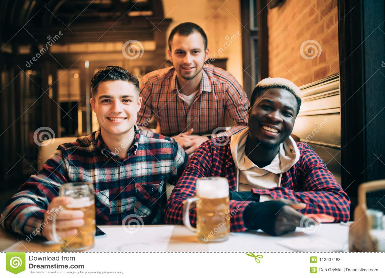 De multiraciale vrienden groeperen drinkend en roosterend bier bij bar Vriendschapsconcept met jongeren die van tijd samen en hav