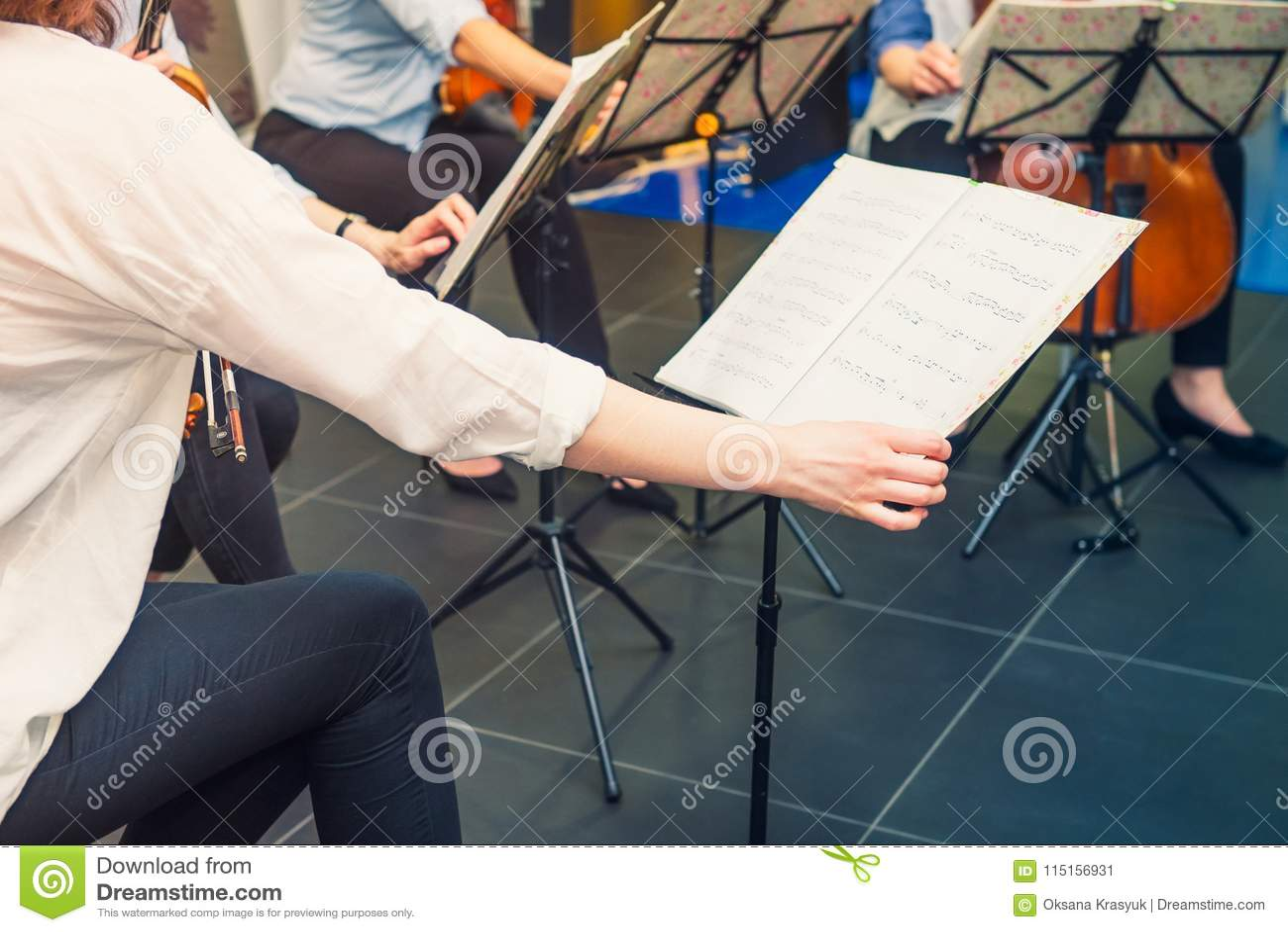 De musicus draait de pagina van Muzieknotitieboekje op tribune met achtergrond van speelcellisten en violistenband op gebeurtenis