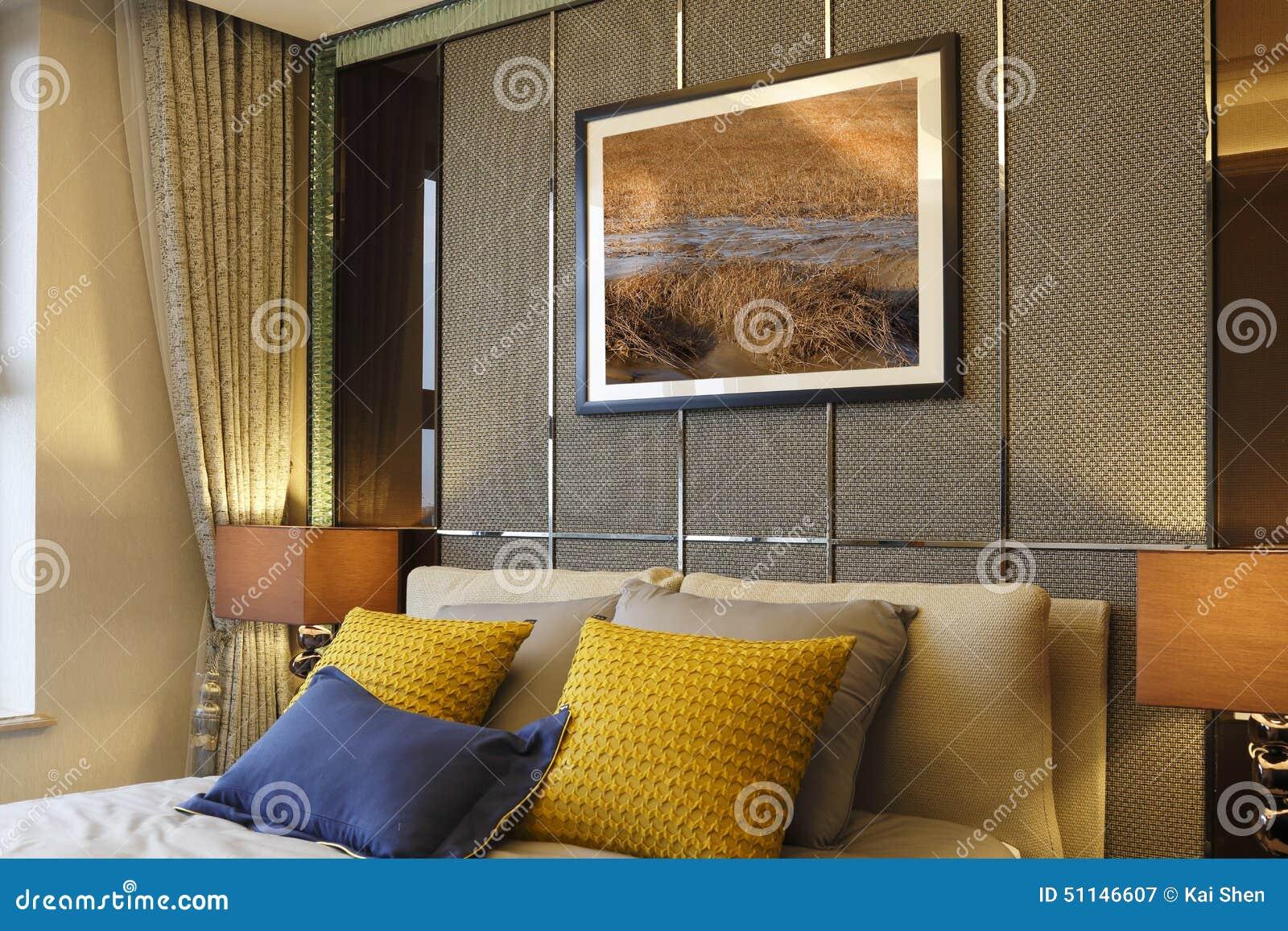 de muur van de slaapkamer de schilderijen de hoofdkussens en de gordijnen