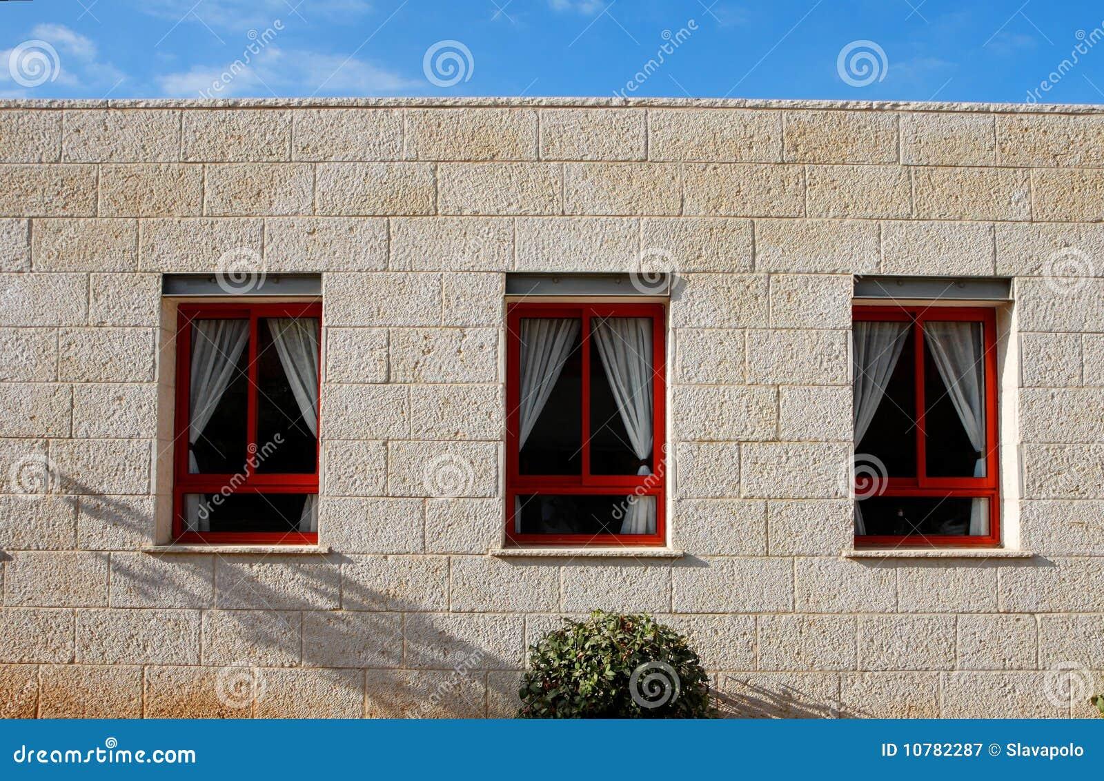 De muur van de steen van het huis met drie vensters