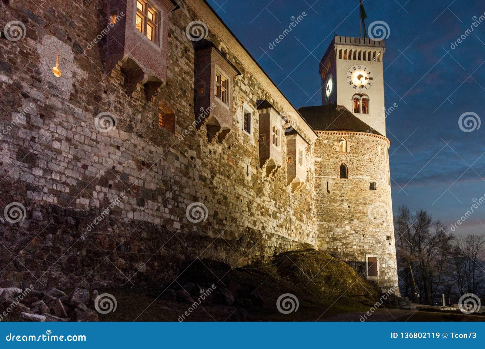 De muur van de kasteelvesting en klokketoren bij nacht
