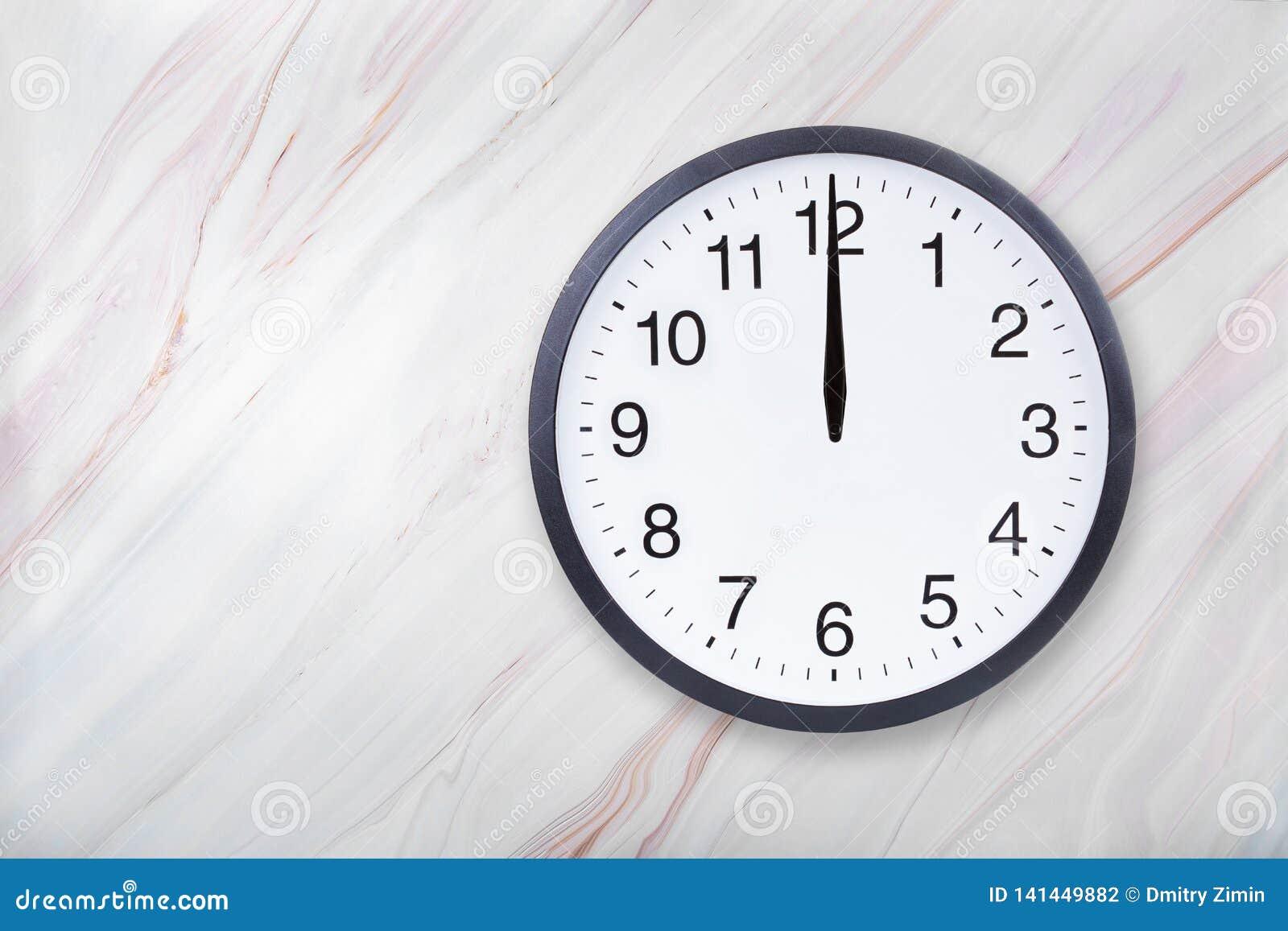 De muurklok op marmeren textuur toont twaalf uur De bureauklok toont middag of middernacht